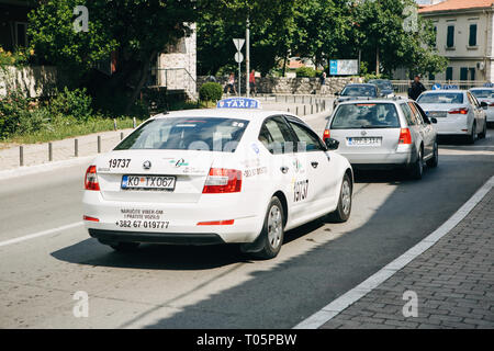 Montenegro, Kotor, June 27, 2018: A taxi car and other cars drive on the road in Kotor. Transportation of passengers around the city. - Stock Photo