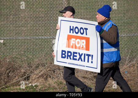 Hartlepool, UK. 17th March 2019. Brexit supporters on the second leg of the March to Leave walk from Hartlepool to Middlesbrough. Nigel Farage was not in attendance.Two men carrying a 'Hoot for Brexit' banner. Credit: David Dixon / Alamy Live News - Stock Photo