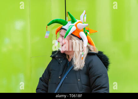 Glasgow, Scotland, UK. 17th March, 2019: A woman wearing a green, white and gold hat celebrates St. Patrick's Day in the city. Credit: Skully/Alamy Live News - Stock Photo