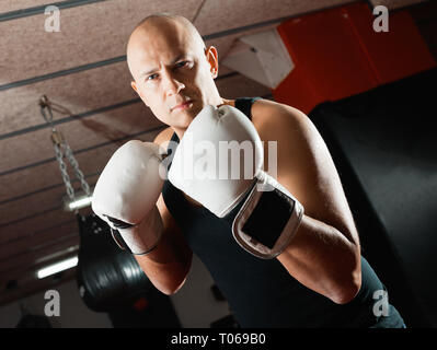 Potrait of positive smiling man boxer who is training in gym - Stock Photo