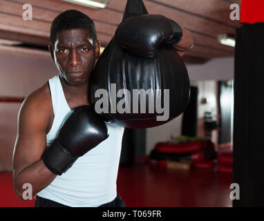 Confident afro american adut  boxer holds training in the ring - Stock Photo