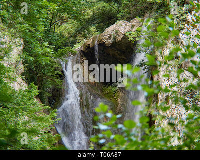 Powerful waterfall falls from the rocks on the spring mountain river. Spring in the mountains. - Stock Photo