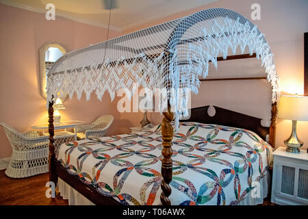 white lace canopy on four poster bed with old-fashioned quilt - Stock Photo