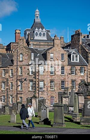 A couple walking through Greyfriars Kirkyard in Edinburgh's Old Town. - Stock Photo