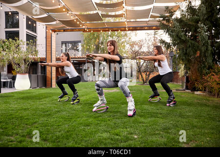 three young ladies,20-29 years old, doing squats in jump boots in a backyard of a a fancy house. - Stock Photo