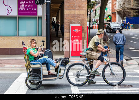 CHARLOTTE, NC, USA-3/16/19: Two young women look at smart phones while riding in a bicycle towed cart in uptown Charlotte. - Stock Photo