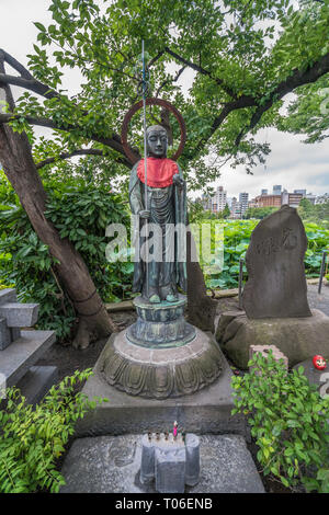 Taito-ku, Tokyo - July 27, 2017: Offerings placed at Monument of Jizo or Ksitigarbha.  Located in front of Shinobazu Bentendo temple, Ueno Park - Stock Photo