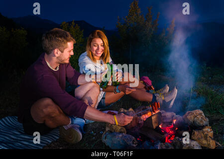 Man and woman cheering with the beer bottles, rosting sausages on the campfire and relaxing by the campfire in the mountain top in the night. Romantic - Stock Photo