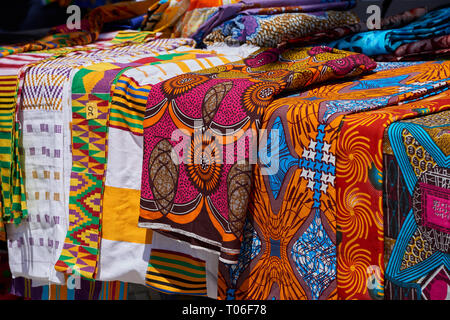 Colorful and vibrant cloth and fabric with dynamic patterns displayed on a street market table. - Stock Photo