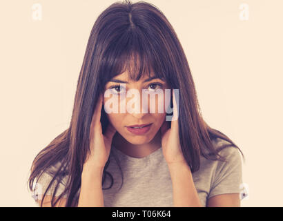 Close up portrait of a young sad woman, serious and concerned, looking worried and thoughtful suffering from migraines. Isolated on white background.  - Stock Photo