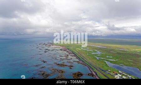 stunning overhead drone shots of the barren and rugged southern iceland coastline and the land, piers and jettys go into the sea. - Stock Photo