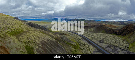 stunning drone shots of an isolated road passes through a volcanic barren landscape in remote Iceland. - Stock Photo