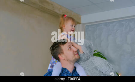 Portrait of funny little girl and her father at home - Stock Photo