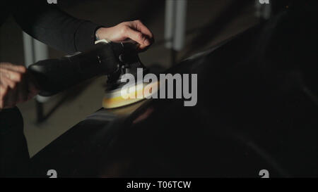 Car detailing - Hands with orbital polisher in auto repair shop. Polished black car. - Stock Photo