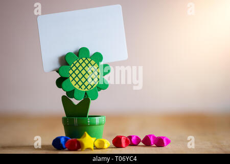 Clip holder card stand green sunflower shaped and multicolored paper stars on wooden table. White plastic blank card in morning sunlight. - Stock Photo