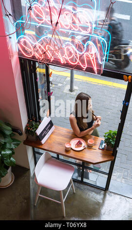 She stood alone before he came. A lonely girl came to the coffee shop to have some cake and juice in the afternoon. She was waiting for her date - Stock Photo