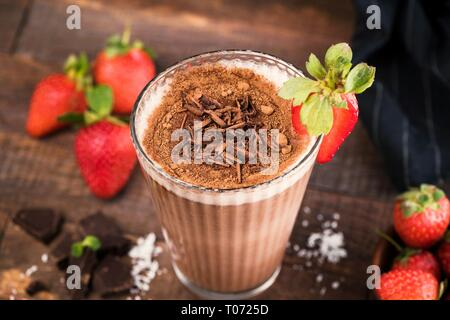 Strawberry Chocolate Milkshake With Chocolate Shavings, Cocoa In Tall Glass On Wooden Background. Closeup view, Selective focus - Stock Photo