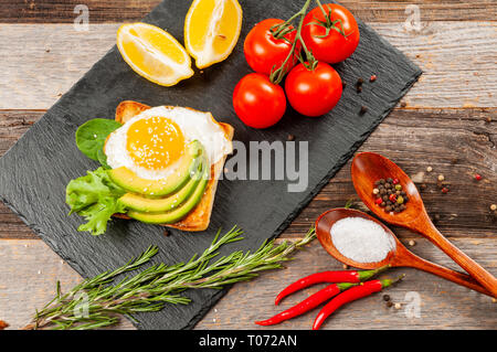 Healthy Breakfast. Fresh sandwich and vegetable. Avocado toast with fried egg - Stock Photo