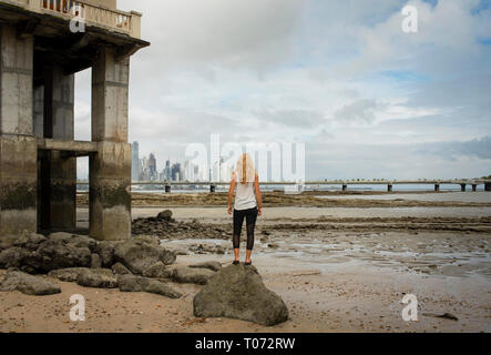 Tourist from behind looking at view over Punta Paitillas skyline. Waterfront of Panama City during low tide. Panama, Central America. Oct 2018 - Stock Photo
