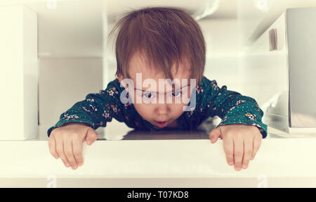Cute caucasian baby girl crawl through tight space under coffee table towards camera.Garbing edge of table and puling her self out. Copy space on righ