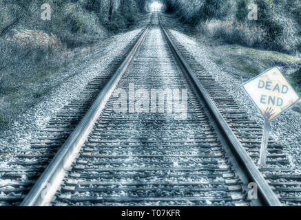 dark and scary railway track with dead end sign in front - Stock Photo
