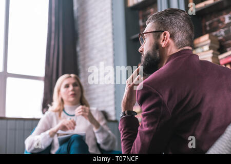 Bearded man feeling thoughtful answering questions of psychologist