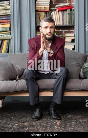 Handsome stylish businessman wearing dark red jacket sitting on sofa - Stock Photo