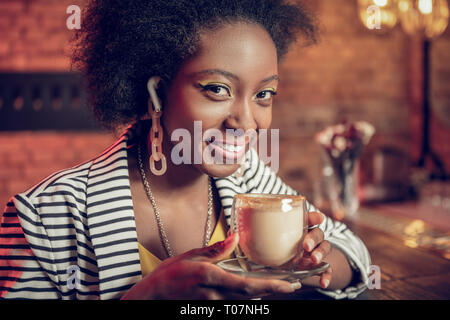 Close-up portrait of African-American girl keeping coffee cup in hands - Stock Photo
