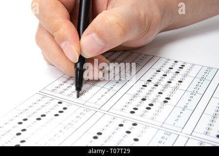 Man is filling OMR sheet handing with pen. - Stock Photo