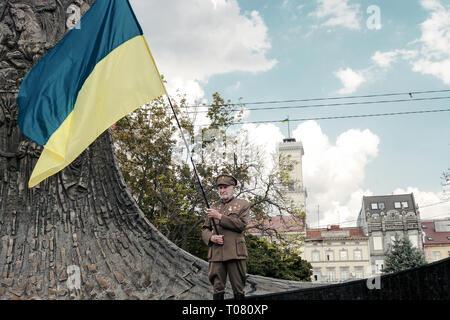 Lviv, Ukraine - 24 August 2018: Ukrainian Independence Day. Senior in military uniform holding national flag - Stock Photo