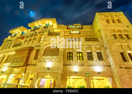 Doha, Qatar - February 18, 2019: facade of historic building at Souq Waqif in traditional Qatari architectural style at night. The souq is considered - Stock Photo