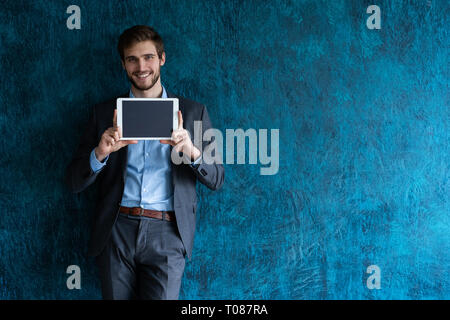 Smiling successful young businessman on blue background in a classic gray suit presenting a tablet. - Stock Photo