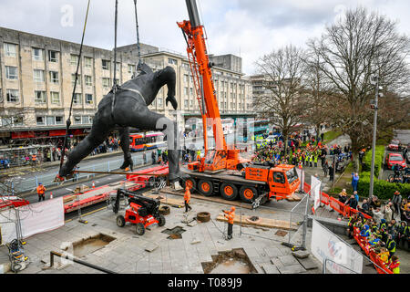 Messenger, the largest bronze cast sculpture in the UK, is lowered into position outside Theatre Royal Plymouth, Devon. - Stock Photo