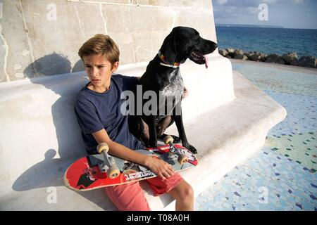 Young boy with skateboard and dog at the beach - Stock Photo
