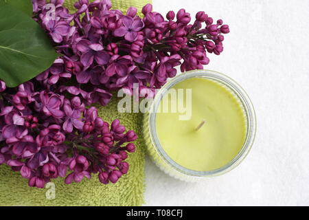 Purple syringa flowers with candles - Stock Photo