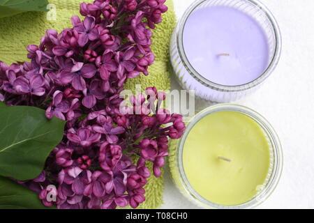 Purple syringa flowers with candles - Stock Photo