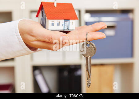 Hand of a woman holds a small house with key - Stock Photo