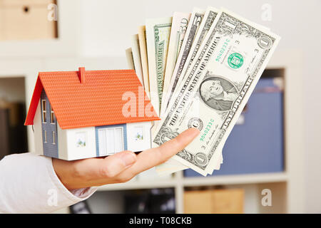 Female hand holds dollars and a small house as a symbol for mortgage lending - Stock Photo