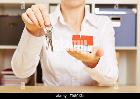 Broker holds a small house and keys in hand - Stock Photo