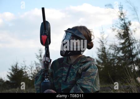 Paintball sport player girl in protective camouflage uniform and mask with marker gun outdoors - Stock Photo