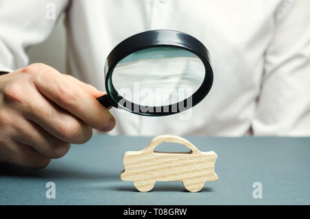 A man holds a magnifying glass over a miniature wooden car. The estimated cost of the auto. Analysis and technical inspection of cars. Buying a new ca - Stock Photo