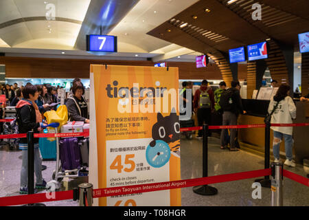 Taipei, Taiwan - February 2019: Passengers queuing at Tigerair check-in counter in Taipei  Taoyuan International Airport. - Stock Photo