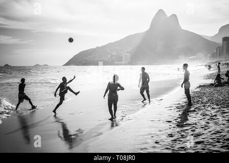 RIO DE JANEIRO, BRAZIL - FEBRUARY 24, 2015: A group of Brazilians playing on the shore of Ipanema Beach, with the famous Dois Irmaos mountain behind them - Stock Photo