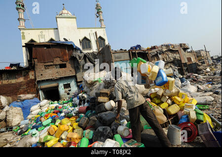 07.12.2011, Mumbai, Maharashtra, India - A man sorts plastic containers for recycling in Mumbai's Dharavi slum with Moinia Masjid in the background, D - Stock Photo