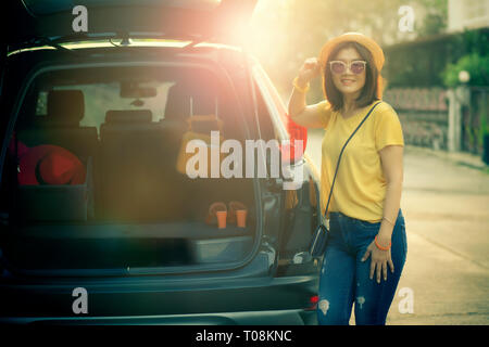 traveller woman toothy smiling face happiness emotion standing on back of suv car ready for road trip on vacation time - Stock Photo