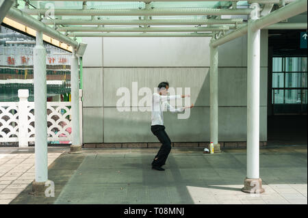 18.04.2018, Singapore, Singapore, Singapore - A man does Tai Chi exercises in a small park outside the People's Park Complex in Singapore's Chinatown  - Stock Photo