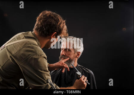 barber cuts a beard to a client to an elderly gray-haired man in the studio - Stock Photo