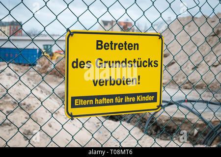 Betreten des Grundstücks verboten ! Eltern haften für ihre Kinder ! gelbes Schild an Zaun von Baustelle. - Stock Photo