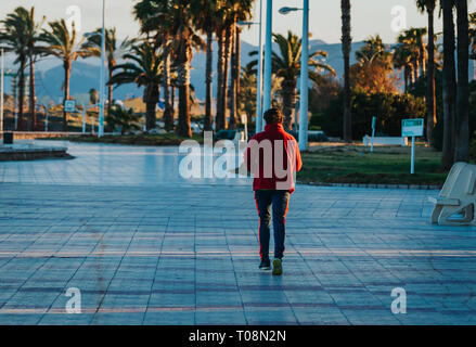 Mature fit male running on a path next to sea with palms in background. Calm spring sunset scenery - Stock Photo