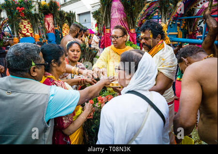 Upon Ganesh Chaturthi festival in Paris, devotees from the hindu community dip their fingers in powder to mark their forehead (tilaka). - Stock Photo